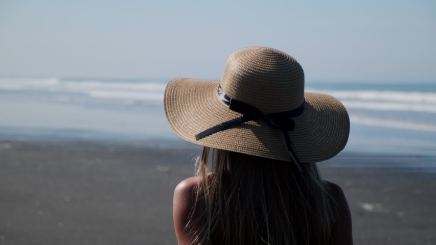 Summer scene with tanned blonde in floppy straw hat, bikini and white shirt having a walk on beach alone. Enjoying the heat, ocean and freedom on vacation