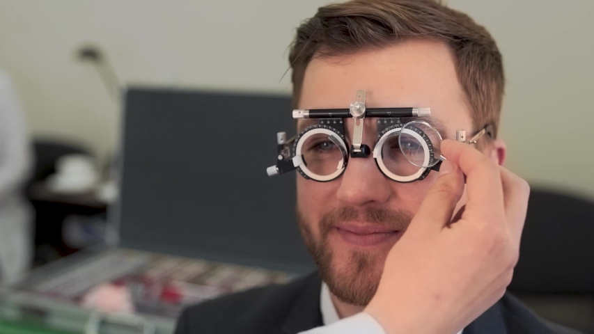Handsome man picks up lenses in ophthalmologist's office | Shutterstock HD Video #1055812712