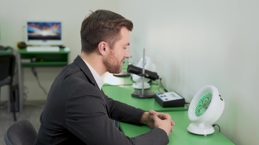 Handsome man is tested on a special apparatus that stimulates vision | Shutterstock HD Video #1055812715
