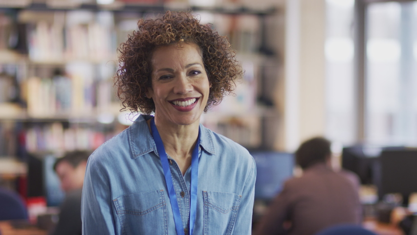 Portrait Of Mature Female Teacher Or Student In Library With Other Students Studying In Background Royalty-Free Stock Footage #1055814026