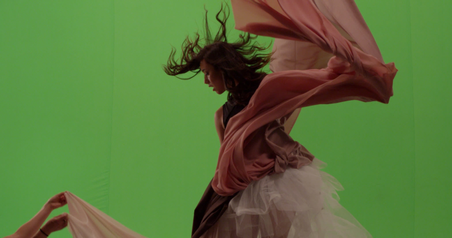 Close up portrait of beautiful fashion model dancer posing against green screen with billowing fabric surrounding her
