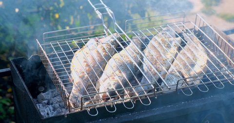 Sea bass or grouper fish grilled over charcoal. Close-up shot cooking seafish with aromatic spices on barbecue grill plate. Baking roasting marinated delicious seafood. BBQ  in summer garden outdoors
