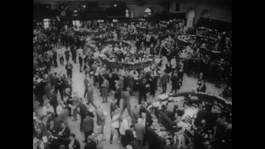 CIRCA 1962 - Men make calls and put in orders on the floor of the New York Stock Exchange in Manhattan, New York.