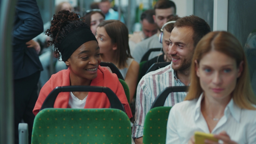 Cheerful diverse young man and woman talking in the tram having fun conversation laughing together inside public transport. Romantic. Date. Urban people.   Shutterstock HD Video #1055854796
