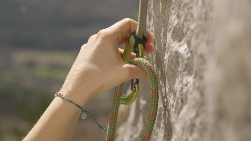 SLOW MOTION, CLOSE UP, DOF: Unrecognizable female rock climber clips her belay rope into a carabiner. Fit woman top roping loops her rope into a safety carabiner. Girl top roping up challenging cliff | Shutterstock HD Video #1055871521