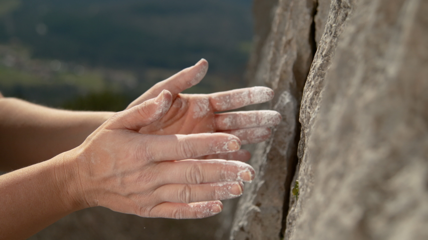 SLOW MOTION, CLOSE UP, DOF: Unrecognizable climber claps her hands to get rid of excess magnesium before continuing her ascent. Woman top rope climbing chalks up her hands midway during her climb