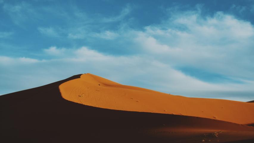 Golden sand and cloudy sky in Sahara desert. Sunset. Beautiful desert landscape. Sahara desert. Sand dunes Arabian desert. Sand dunes wave pattern. Nature background, Morocco, 4k