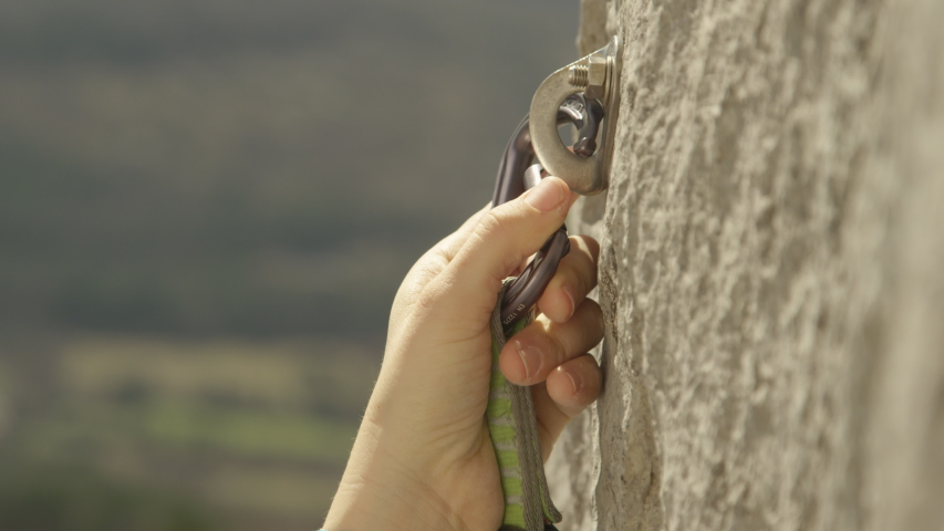 SLOW MOTION, CLOSE UP, DOF: Rock climber clips a carabiner into a bolt screwed into the cliff. Lead climber quickdraws a carabiner into a bolt. Unrecognizable fit woman clips carabiner into a bolt. | Shutterstock HD Video #1055899571
