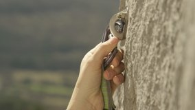 SLOW MOTION, CLOSE UP, DOF: Rock climber clips a carabiner into a bolt screwed into the cliff. Lead climber quickdraws a carabiner into a bolt. Unrecognizable fit woman clips carabiner into a bolt.