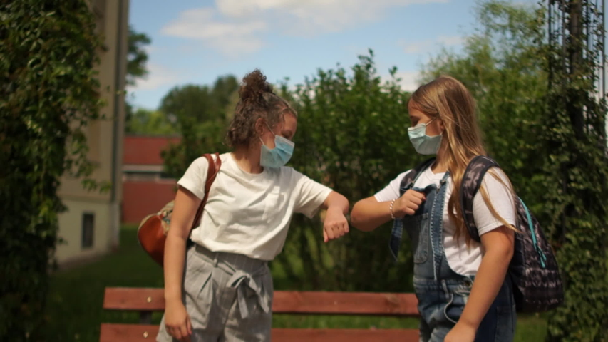 Two beautiful girls, masked teenagers are greeting non-contact, social distance, back to school, pots-quarantine life Royalty-Free Stock Footage #1055901695