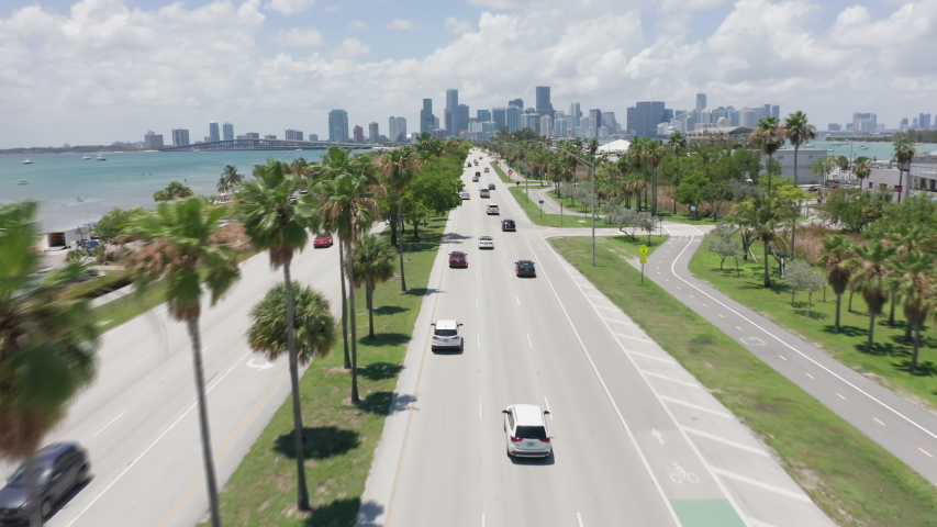 4k drone flying between green trees above cars driving by the road in Miami downtown direction on sunny day. Aerial cityscape view. Beautiful background for transportation business, Miami Florida USA