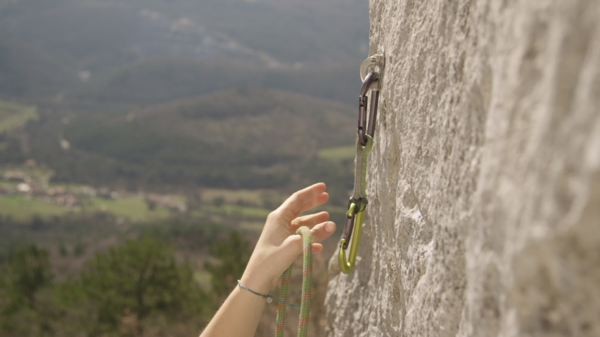SLOW MOTION, CLOSE UP, DOF: Unrecognizable female climber hooks a carabiner into metal bolt and attaches her belay rope. Woman lead climbing attaches a carabiner and belay rope while climbing up cliff
