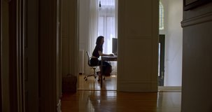 Attractive young woman enjoying what she is doing as she works on her computer in her beautiful Brownstone apartment