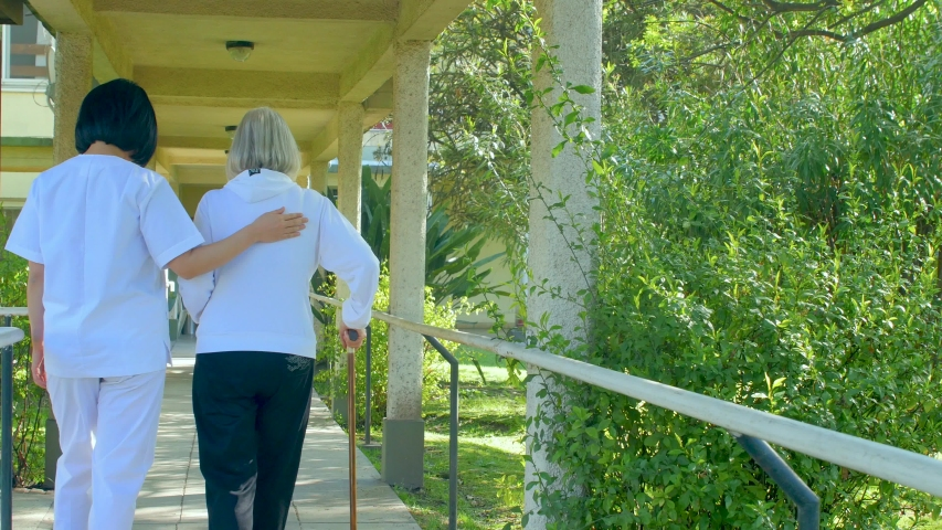 Nurse helping elderly woman with crutches at hospital. Back view Royalty-Free Stock Footage #1055907737