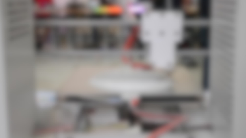 Blurred background. 3d printer printing white round model backside. Many people in the background blurred plan close-up.