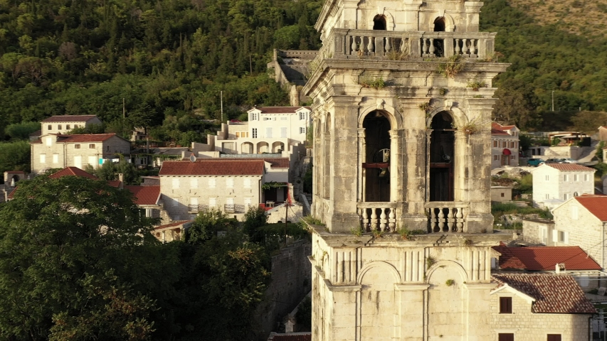 Perast. Montenegro. Sunset. Old medieval town with red roofs by beautiful Kotor bay on the coast of Adriatic sea.  Aerial footage.