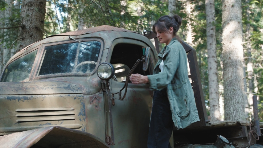 Woman checking old truck in forest. Young ethnic female looking inside abandoned military vehicle on sunny summer day in forest