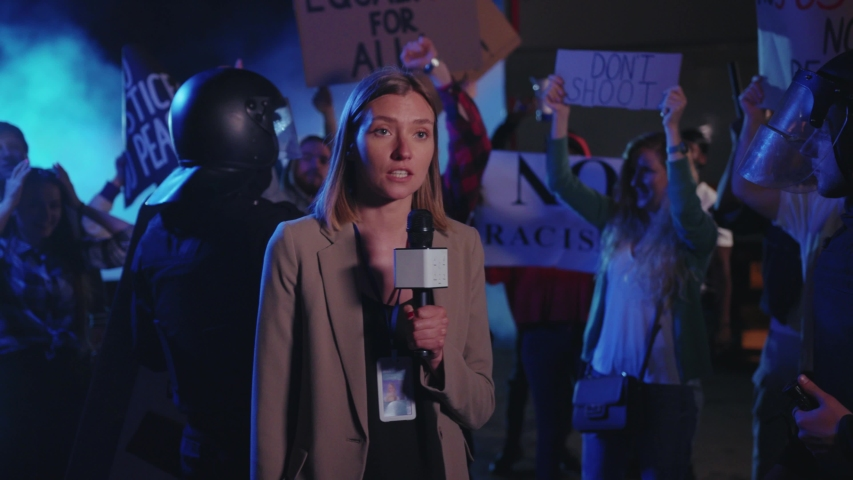 Beautiful serious woman journalist making a live speech on TV explaining the situation with night street demonstration rally. No racism. Black lives matter. Shocking news.