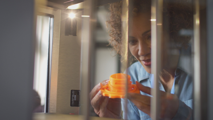 Mature female college student studying engineering using 3D printing machine - shot in slow motion