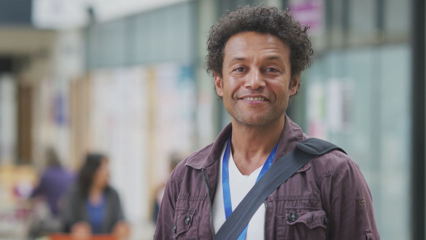 Portrait of smiling mature male teacher or student with backpack in college hall - shot in slow motion
