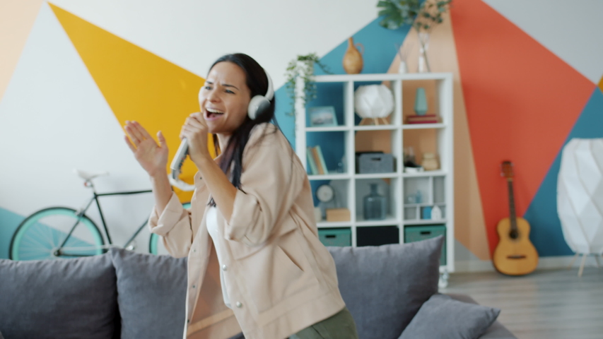 Slow motion of happy young lady in headphones dancing and singing in remore control having fun in apartment. People, lifestyle and joy concept. Royalty-Free Stock Footage #1055921918