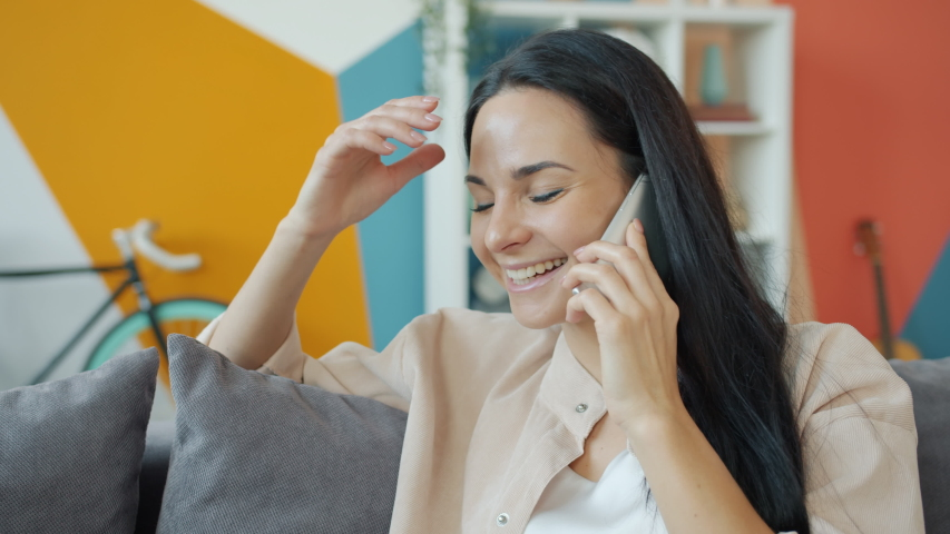 Slow motion of young woman talking on mobile phone and laughing at home enjoying modern communication. Happy youth, flat and lifestyle concept. | Shutterstock HD Video #1055922005