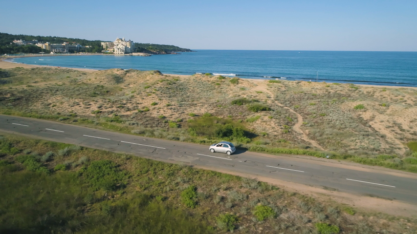 Aerial view of car driving on coastal road next to beautiful wild beach Royalty-Free Stock Footage #1055922023