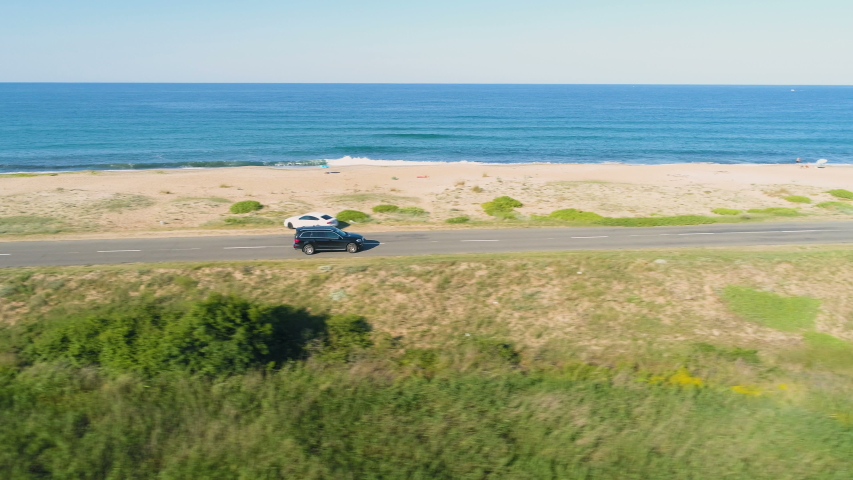 Drone chasing fast driving black SUV along coastal asphalt road with crashing waves in the background Royalty-Free Stock Footage #1055922026