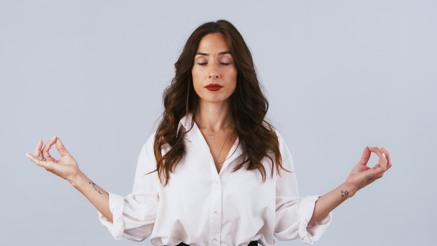 Female in white shirt is looking tired, showing gyan mudra hands gesture, meditating with closed eyes. Posing on gray background. Close up | Shutterstock HD Video #1055923526