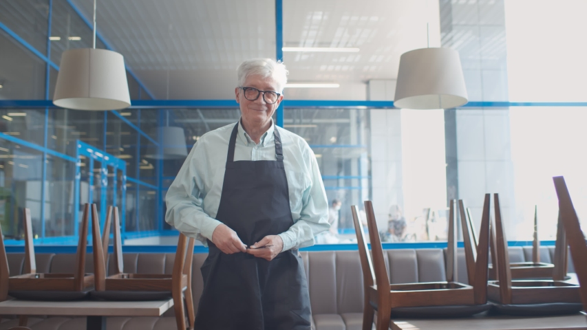 Mature man small business owner arranging apron walking in closed cafe. Senior male restaurant manager preparing for opening new place or reopening after quarantine