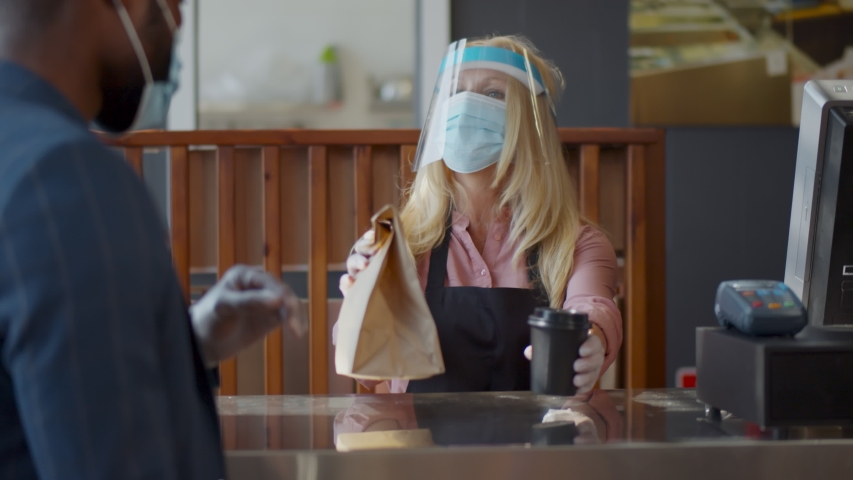 Mature waitress in face shield and mask giving takeaway bag and coffee to customer at cafe. Small cafe owner working in protective wear reopening after lockdown during quarantine | Shutterstock HD Video #1055924993