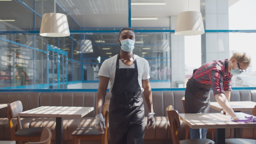 Portrait of african waiter in apron safety mask and gloves walking in cafe with colleague wiping table with cloth on background. Small business during quarantine concept Royalty-Free Stock Footage #1055925002
