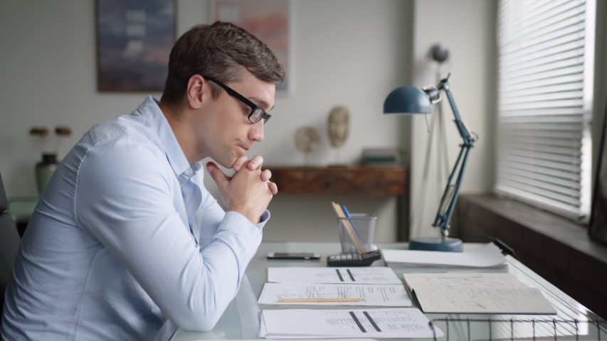 Young serious business man with glasses sits at table in office, works with papers. has difficulties, gets upset because of failure and problems, shakes head. side shot | Shutterstock HD Video #1055925359