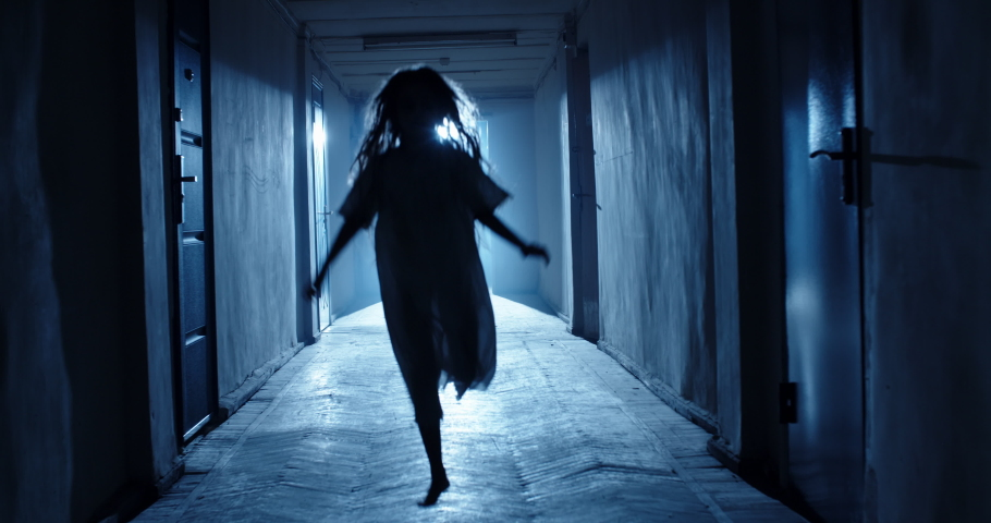 Little girl in white dress looking like a ghost carelessly running down the hallway of a haunted house - halloween costume party, horror movie 4k footage   Shutterstock HD Video #1055928185