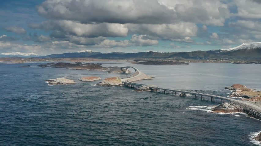 An aerial view of the Atlantic road in Norway. A curved bridge spanning above the turbulent waters, connecting two islands. White-gray clouds hanging above. A lone caring on the road. Mountains