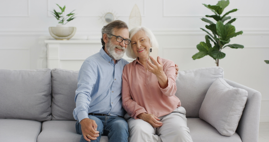 Caucasian senior man and woman woman on retirement. Happy couple sitting on sofa and posing with smiles to phone camera at home. Old couple taking selfie photos with smartphone.
