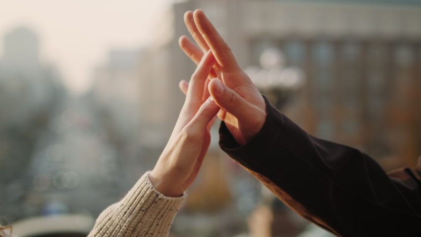 Love couple hands connecting in urban background. Unrecognizable man and woman hands holding outdoors. Closeup romantic people touching hands outside. | Shutterstock HD Video #1055931365