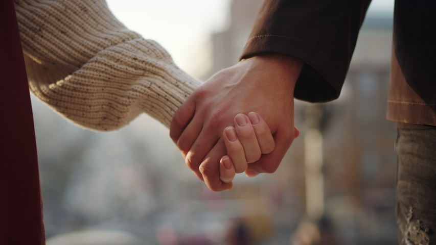 Love couple holding hands on urban background. Closeup guy and girl hands meeting on city street. Unrecognizable man and woman touching hands outdoors.
