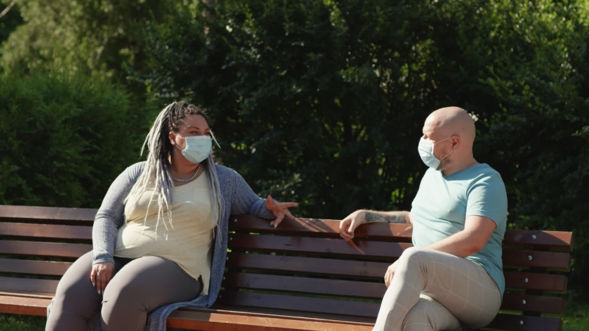 Pandemic concept. Two happy friends in medical mask keep social distance sitting and talking outside on bench in park at summertime. Couple prevent themselves from coronavirus covid spread. Royalty-Free Stock Footage #1055935907