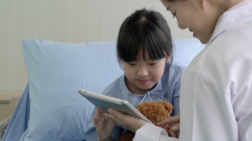 Asian doctor nurse pediatrician woman visiting child girl patient and empathy to the diagnosis when visit doctor. Concept of medical, healthcare, healthy family, pediatric checkup and hospital office.