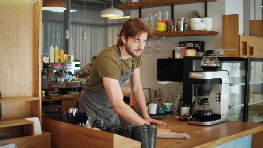 Young barista man in apron cleaning and preparing bar for visitors working in coffee shop, sanitizer desinfection during coronavirus covid 19 pandemic, reopen business, post covid | Shutterstock HD Video #1055936831