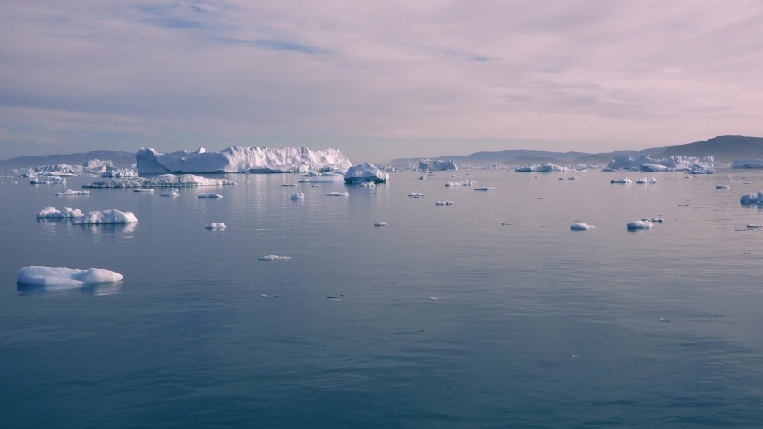 Greenland. Icebergs. Nature and landscapes of Greenland. Disko bay. West Greenland. Summer Midnight Sun and icebergs. Big blue ice in icefjord. Affected by climate change and global warming.   Shutterstock HD Video #1055938856