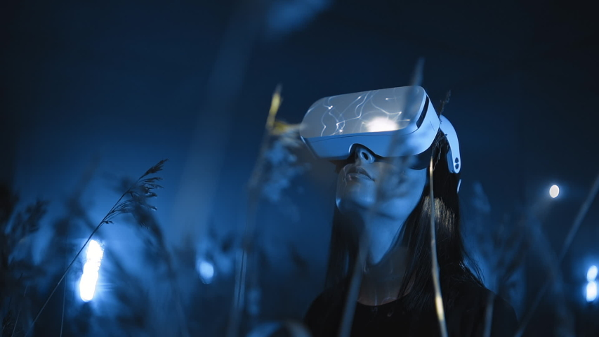 portrait of girl in VR headset or glasses looking around at night in nature in forest or field, modern technologies of virtual or augmented reality 3D graphics and holographic projection Royalty-Free Stock Footage #1055939249
