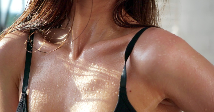 Athletic beautiful body of sexy caucasian fitness woman in top doused shoulders, collarbones with water, close-up drops of sweat and perspiration on skin after gym training, slow motion. Workout girl