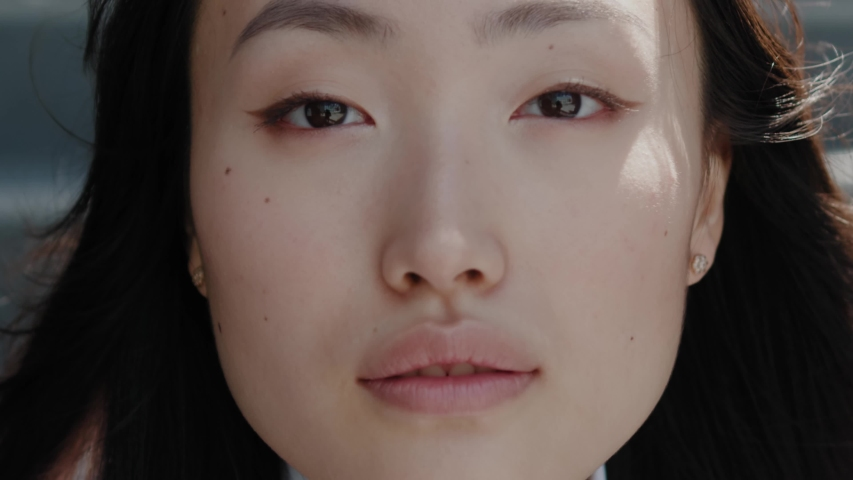 Face of beautiful soft chinese woman with natural make-up looking at camera. Portrait young asian pretty brunette girl outside at sunshine. Etnnicity. People. Beauty. | Shutterstock HD Video #1055939516