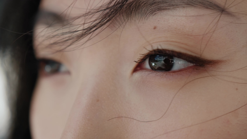 Eyes of wonderful asian young woman opening and looking straight. Beautiful face of chinese sensitive lady outdoors. Ethnicity. Close-up.