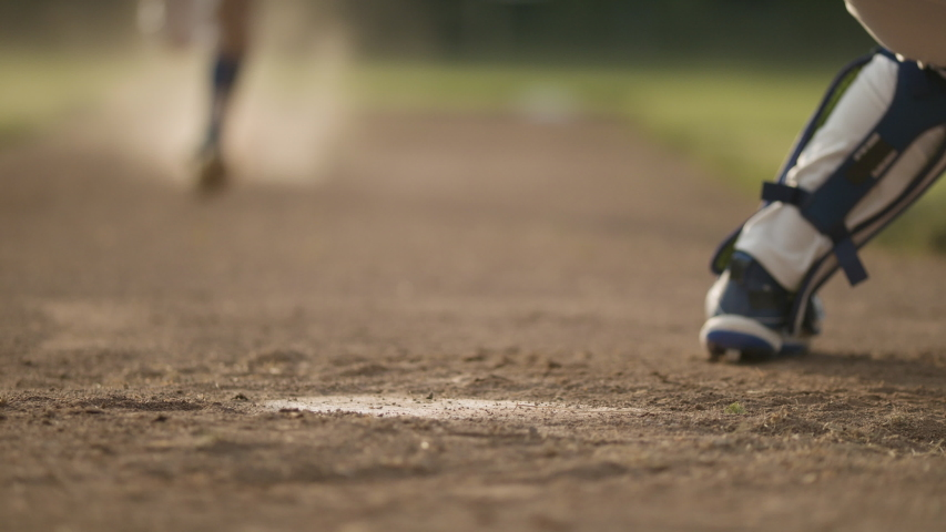 Sliding into home. A runner tries to slide into home plate. Back catcher tags the runner and it's a close call in a dustup. Shot in slow-motion and in 4k.