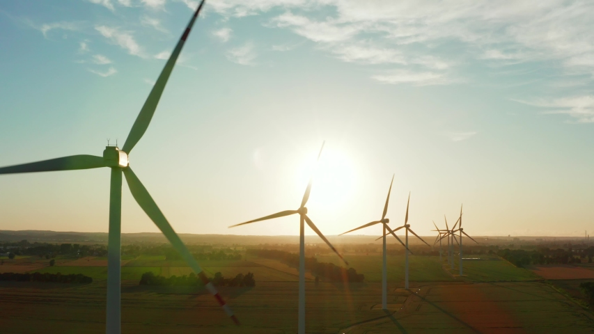 Drone Flies Over a Windmill Park at Sunset. Aerial View of a Farm With Wind Turbines Standing on a Wheat Field. Wind Power Turbines Generating Clean Renewable Energy for Sustainable Development. | Shutterstock HD Video #1055942822