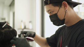 Asian male barber cutting male customer hair at Barbershop wear black protective mask. job opportunity Professional, Barber industry during Corona virus Pandemic Covid-19 re-open start up business