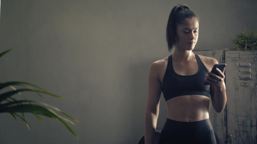 Woman using smart phone with personal trainer workout app at home. Woman preparing for workout using fitness app. Close orbit shot.Woman using mobile phone while resting during fitness training
